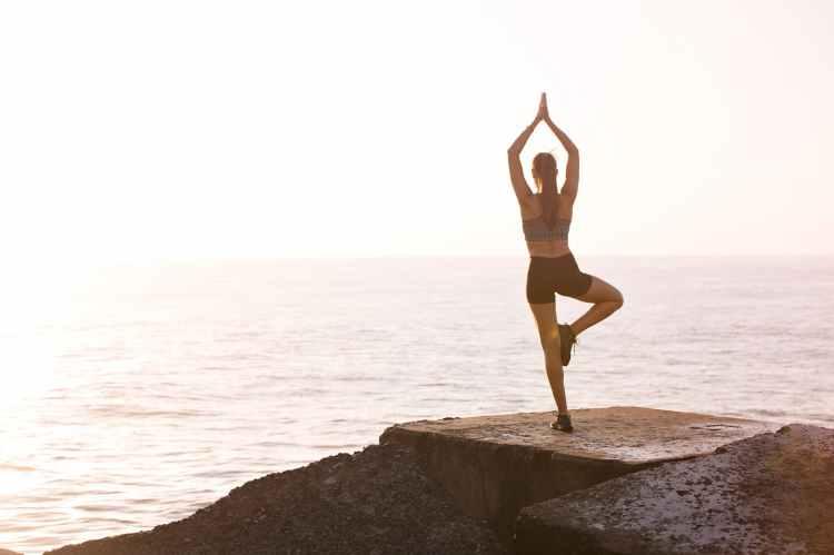 woman meditating on rock near body of water